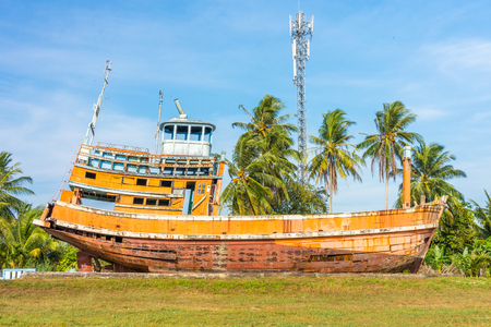 Orange abandoned fishing boat ruin in Phang Nga, Thailand. It was damaged in the last tsunami. Editorial