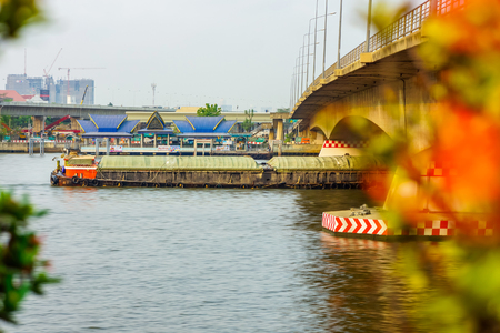 Cargo Ship under road bridge on Chao Phraya river. The one of transportation in Thailand.