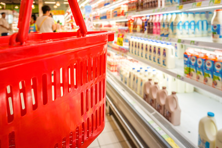 browses: Shopping with empty red plastic basket in superstore. Customer browses the goods in food and beverage department.
