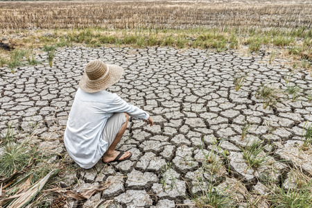 Sad farmer is sitting in a agricultural field during the long drought. Because of the lack of water in area.
