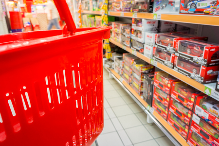 browses: Shopping with red plastic basket in shopping mall. Customer browses the goods in toys department.