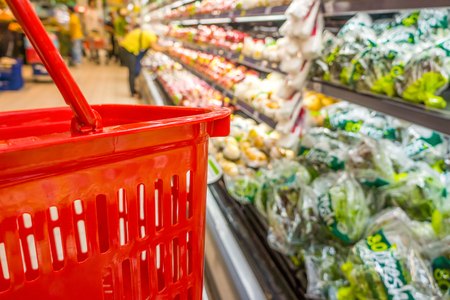 browses: Shopping with empty red plastic basket in supermarket. Customer browses the goods in food and beverage department. Stock Photo