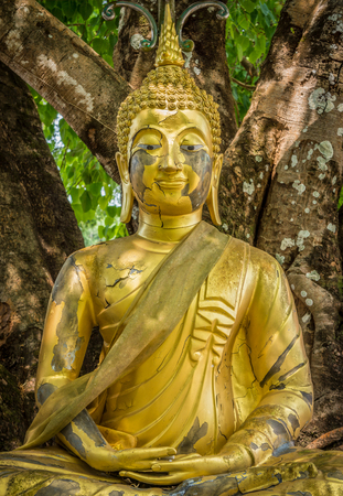 persuading: Ancient cracked statue of Buddha image. The old Buddhism ruin in Thailand.