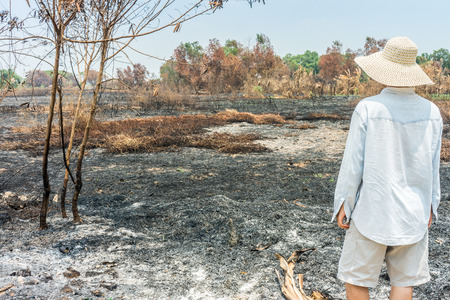 Unfortunate farmer looking to his burnt agricultural field. The area was damaged from bushfire. Stock Photo