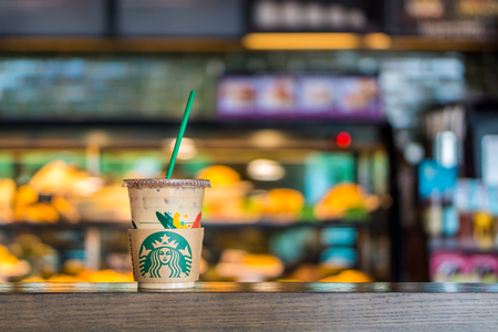 BANGKOK, THAILAND - JULY 2, 2017: Starbucks plastic cup with straw of Iced Caffe Espresso Beverage on table in coffeeshop. Starbucks is an American coffee company and coffeehouse chain.
