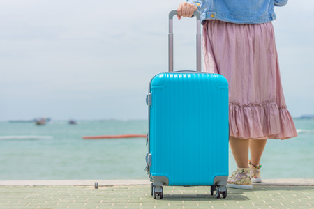 Modern blue travel baggage pulled by woman on beach. It is made from thermoplastic polymers .
