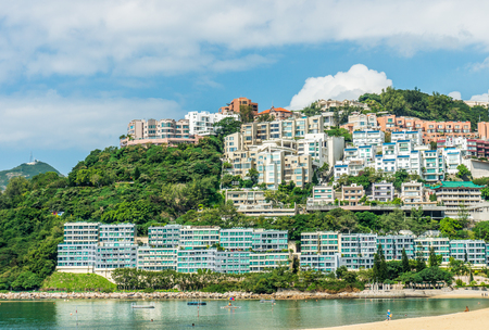 waterfront property: Luxury residences on waterfront and mountain with views of Repulse Bay and beach. The houses feature a contemporary classic architectural style with detail articulation of moldings and fenestration.