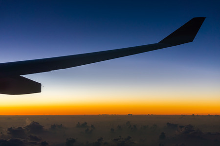 fixed line: Silhouette image of airplane fixed wing. It is flying over cloud in the sky.