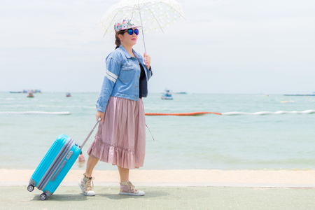 Smiling Women or tourist is holding umbrella and pulling modern blue rolling hard baggage. She is on pavement at beach.