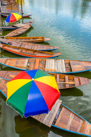 Vintage Asian paddling boats with colorful parasols in lake. They are made of wood.