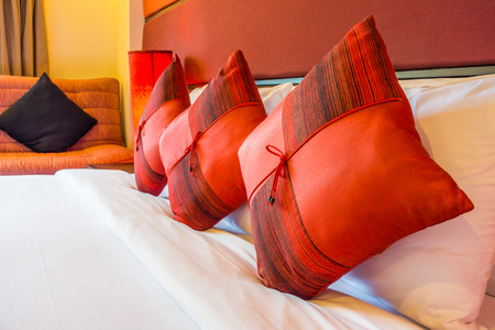 Red cushions on double bed in master bedroom. The modern design of luxury room. Stock Photo