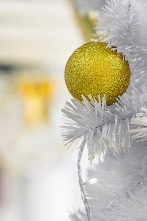 Closeup of golden Christmas baubles on white branches with empty space. Lights and spherical decorations are used to festoon a tree.