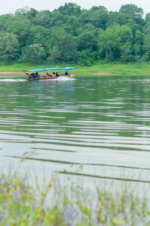Vintage tourist long-tailed boat with travelers on lake. Tourism at Kaeng Krachan Reservoir National Park in Phetchaburi, Thailand, Southeast Asia.