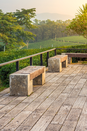 Modern seats constructed with wood log and concrete. They are on deck or patio.