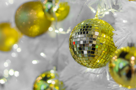 Glass Christmas baubles on white branches. Lights and spherical decorations are used to festoon a tree.