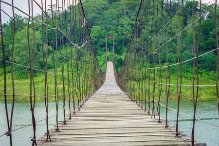 paso de peatones: En un largo puente de madera de suspensión sobre el lago natural. Está en el Parque Nacional Kaeng Krachan Reservoir en Phetchaburi, Tailandia, sudeste de Asia.