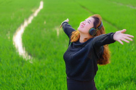 Happy Asian girl raising arms is listening to music with headphone. She is in paddy field of Thailand.