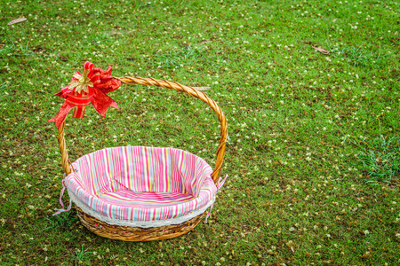 basketry: Empty gift basket with bow and napery. It is on a lawn.