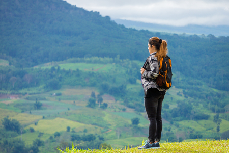 Woman with backpack on hilltop at Khao Ta-Khian Ngo Viewpoint. The location in Khao Kho District, Phetchabun, Thailand, Southeast Asia.