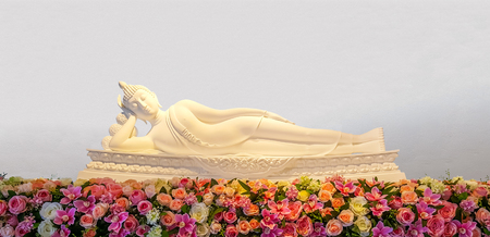 The statue of Reclining Buddha and flowers. This posture also called the Nirvana Buddha. Stock Photo