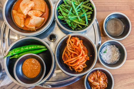 Top view of Korean side dishes filled with rich flavors, fresh and pickled vegetables. They are separated in small plates or bowls. Stock Photo