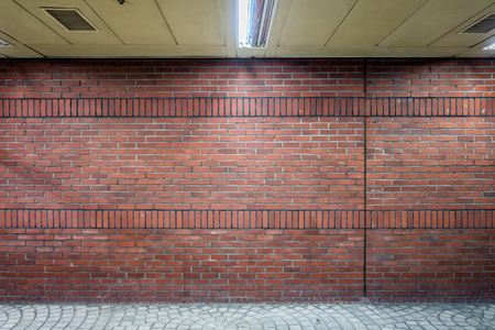 Dark brick wall in indoor walkway. The bricklayer pattern made by mixed stretchers and soldiers. Фото со стока