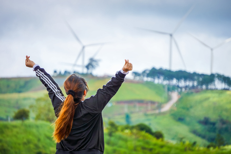 Woman feels free and powerful in front of wind farm. Location in Khao Kho District, Phetchabun, Thailand, Southeast Asia.
