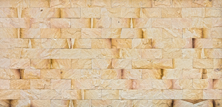 Natural yellow rock wall. The exterior decoration of many building.