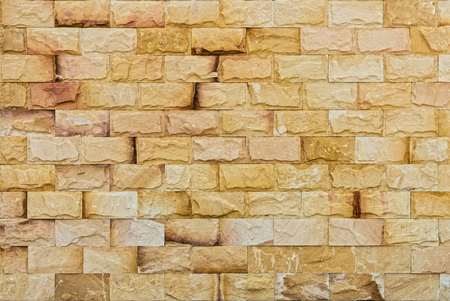 Natural yellow rock fence. The exterior decoration of many building.