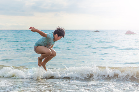 Fat young Asian boy is jumping over wave. Child is playing alone on a beach.