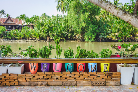 Colorful welcome alphabets on potteries at riverside. They are near river in countryside of Thailand.