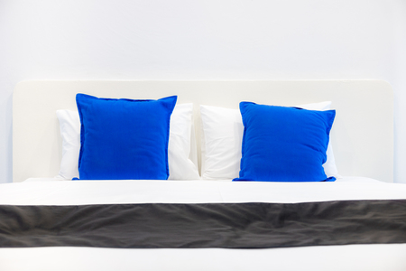 Front view of white pillows and blue cushions on bed in a bedroom. The plain design of romantic light pale room.