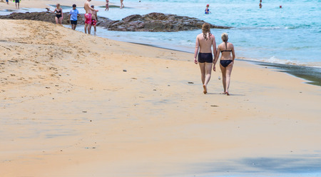 Couple in swimming suits walking on a beach. Tourist seaside attraction of Andaman sea in Thailand. 免版税图像