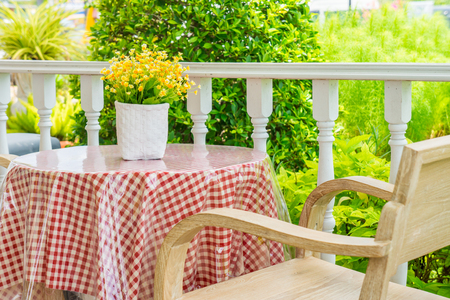 Artificial flowers and vase on table with wooden armchair. They are on a porch for decoration. Stockfoto