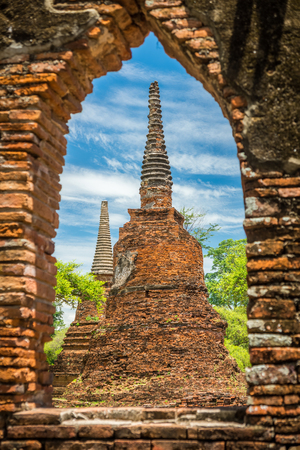 Two ancient remains pagodas looked through ruin window in Wat Phra Si Sanphet, Ayutthaya, Thailand. It is built in the classic, Ceylonese design or bell shape.