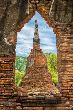 The ancient remains pagoda looked through ruin window in Wat Phra Si Sanphet, Ayutthaya, Thailand. It is built in the classic, Ceylonese design or bell shape.