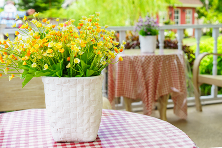Artificial flowers and vase on table. They are on a porch for decoration. Stockfoto