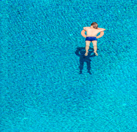 High angle view of young man sleeping on lifebuoy in swimming pool. He is relaxing on vacation. Archivio Fotografico