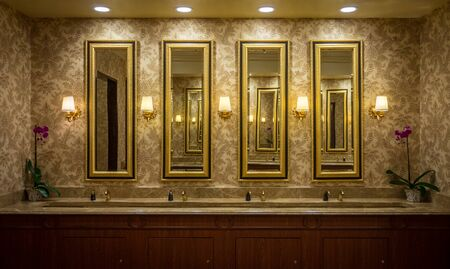 New contemporary restroom with . It consists of touch-free automatic sensor faucets, long mirrors, washbasins, granite countertop, warm light lamps and flowerpot.