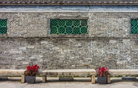Traditional Chinese brick fence or wall with ventilation holes and stone benches. An old exterior decoration in Macau, China.