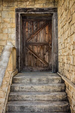Door entrance with ancient European style. It consists of wooden door, stone wall and stairs.