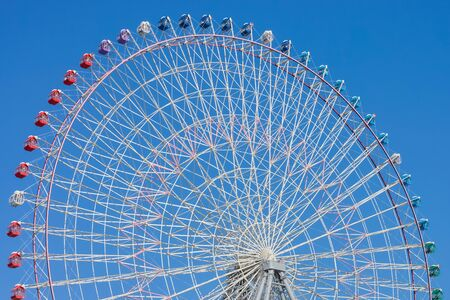 Giant ferris wheel with blue sky. Massive amusement ride with multiple passenger cars. Stockfoto