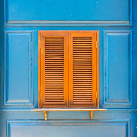Closeup of traditional wooden casement window with slat blinds on blue wall. Exterior decoration of classic Italian style.