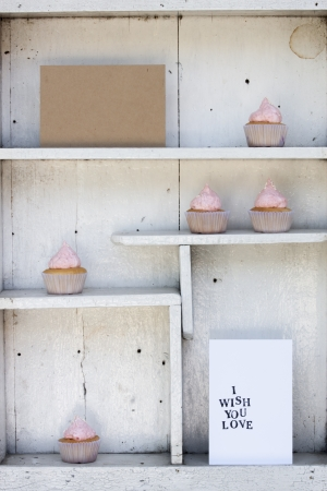 White vintage shelf with a card and strawberry cream cupcake photo
