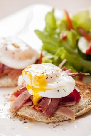 Eggs Benedict met gerookte spek, en salade
