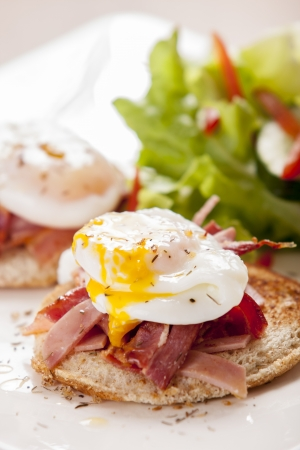 Eggs Benedict with smoked bacon, and salad Фото со стока - 17957525