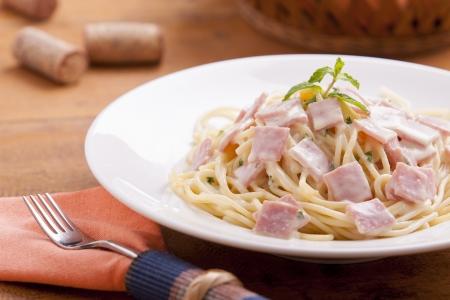 Spaghetti Carbonara on a white plate with ham