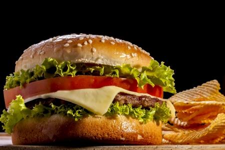 Hamburger met chips focus op front in zwarte achtergrond