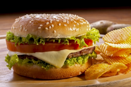 cheeseburger with fries: Burger with chips on wooden plates,and black background