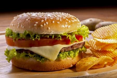 Hamburger met chips op houten platen, en een zwarte achtergrond